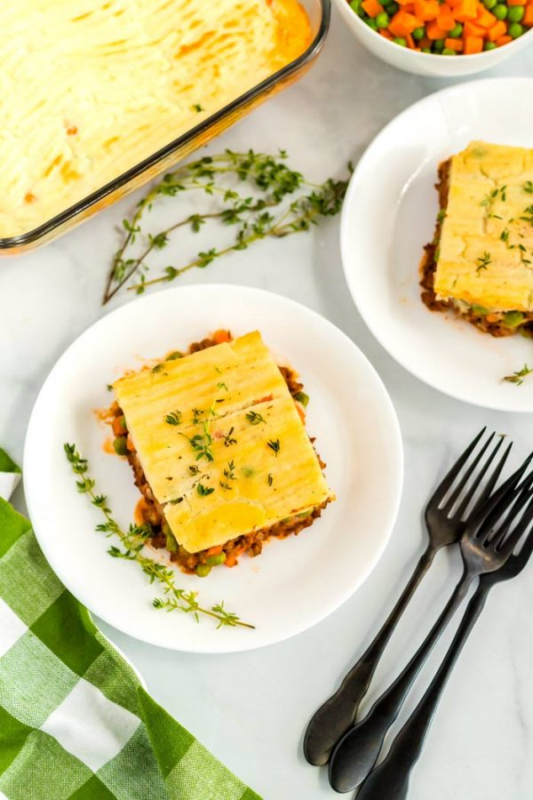 Slices of shepherd's pie on white plates.
