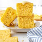 Cornbread pieces stacked on top of each other with a pad of butter on top that is starting to melt.