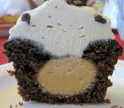 Chocolate cupcake cut in half with a peanut butter bonbon in the center.