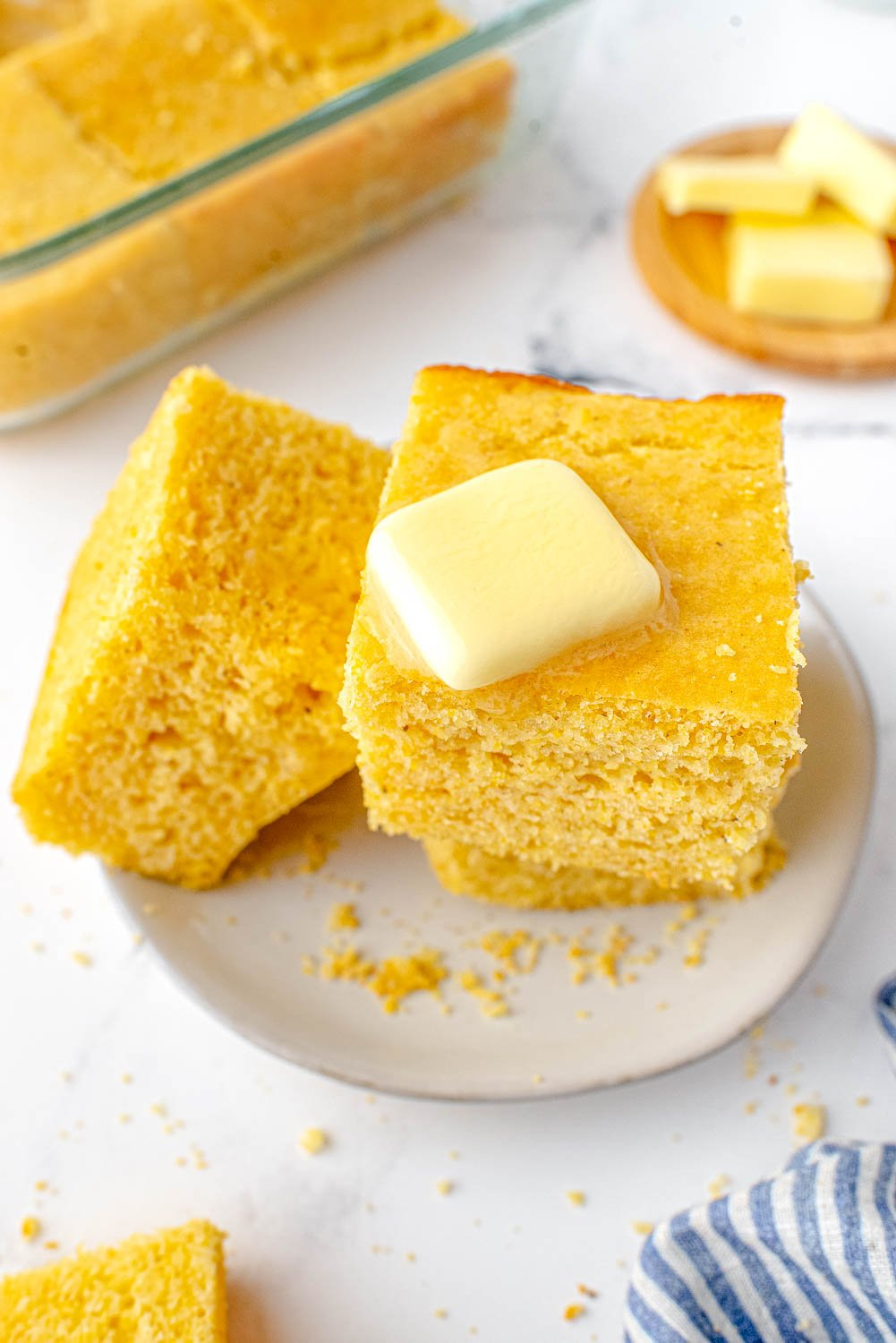 An over head picture of a piece of cornbread with melted butter on it.
