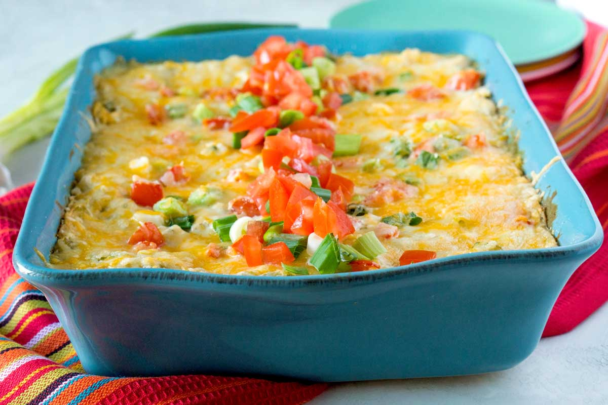 Stacked Green Chile Chicken Enchilada Casserole in a blue pan.