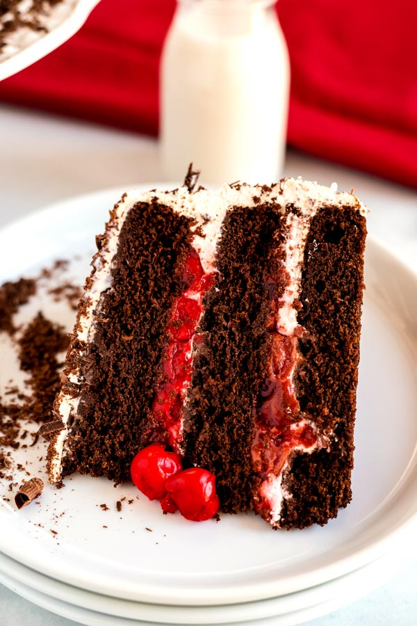 A slice of Black Forest Cake on a white plate with extra cherries.