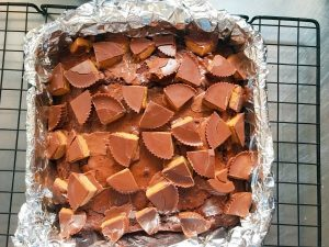 Place peanut butter cups on baked brownies.