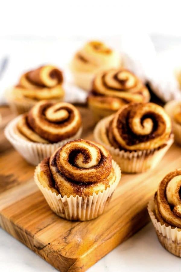 Cinnamon rolls on a wood cutting board.