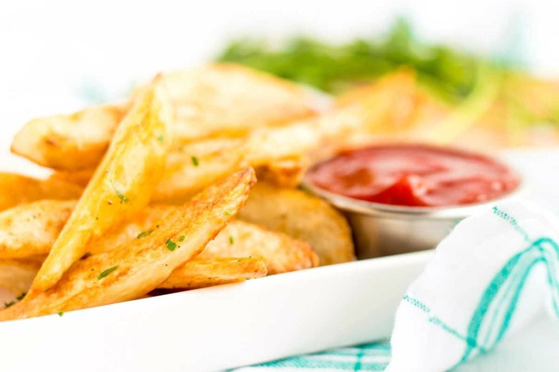 Oven Fries on a white tray with ketchup.