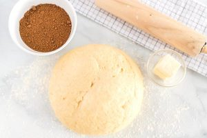 The dough on a floured surface with a rolling pin and the cinnamon sugar filling.