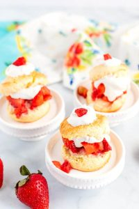 Shortcakes on pedestals with strawberries surrounding them.