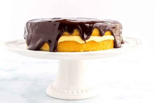 Finished Boston Cream Pie Recipe on a cake pedestal.