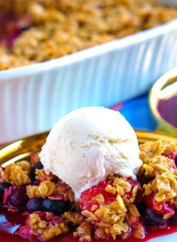 Berry crisp on a plate that is served with ice cream.