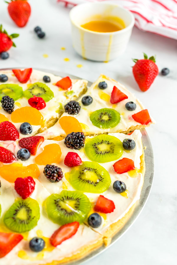 Cut the fruit pizza into slices and serve.