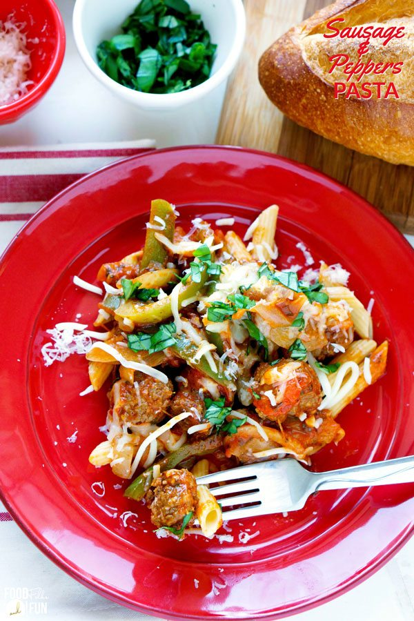 Pasta with sausage, peppers, onions, cheese, and basil on a plate.