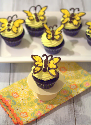 A dark chocolate butterfly cupcake on a mini cake stand with more on a serving platter in the background