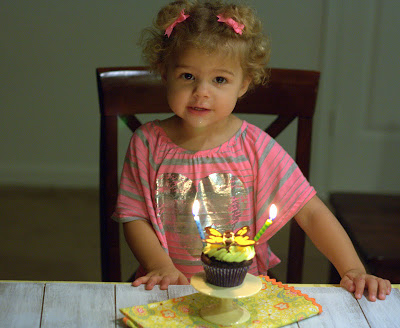 A toddler with a dark chocolate butterfly cupcake on a mini cake stand for her birthday