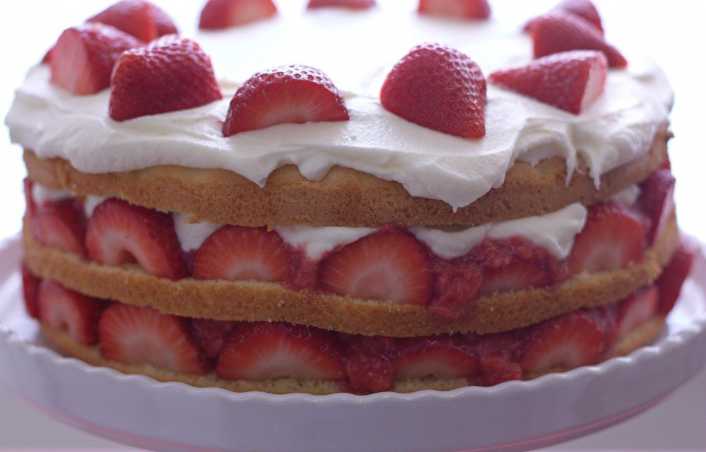 A close up of Strawberry Cream Cake on a cake stand