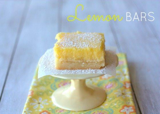 A lemon bar on a cake plate