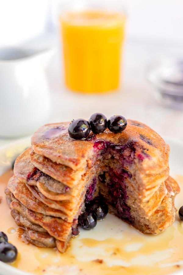 A stack of buckwheat pancakes with a large slice taken out of it.