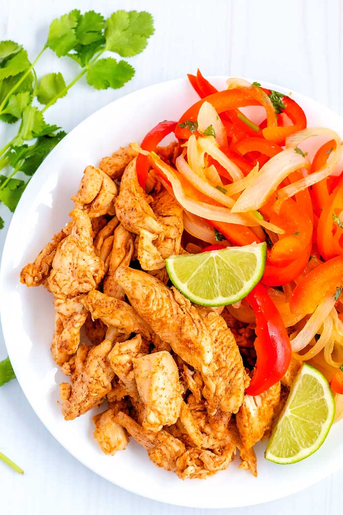 Easy chicken fajita strips and onion and bell pepper strips with lime wedges.