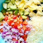 All of the pasta salad ingredients in a bowl ready to be mixed.