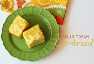 2 pieces of Sour Cream Cornbread on a green plate.