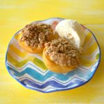 Baked Peaches with Oat crumble topping and a scoop of vanilla ice cream on a plate