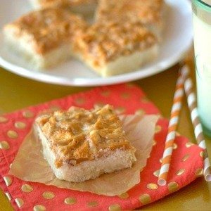 a slice of Caramel Cashew Shortbread bars on a napkin with more on a plate in the background