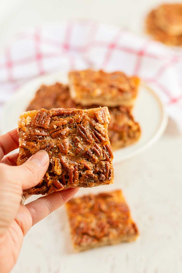 Holding up a Pecan Pie Bars with Shortbread Crust.
