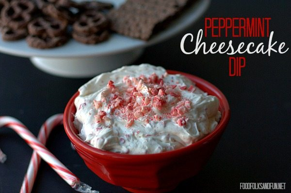 Peppermint Cheesecake Dip with candy canes and chocolate covered pretzels in the background.