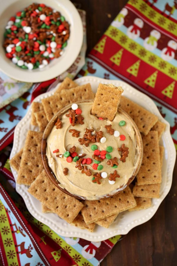 Gingerbread cheesecake dip with a bowl of Christmas sprinkles.