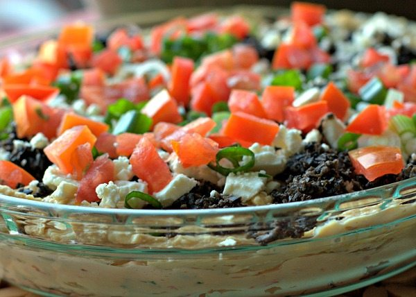 A close-up of 7 layer Greek Dip in a shallow dish