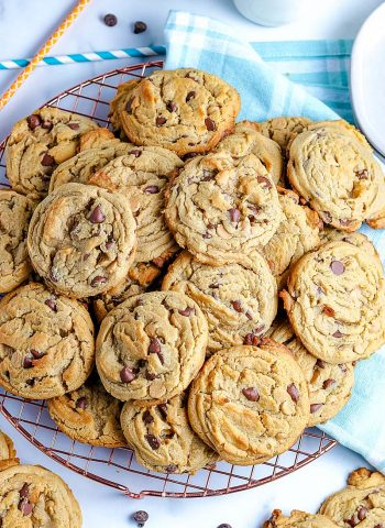 Best Peanut Butter Chocolate Chip Cookies EVER! They're piled high on a wire rack.