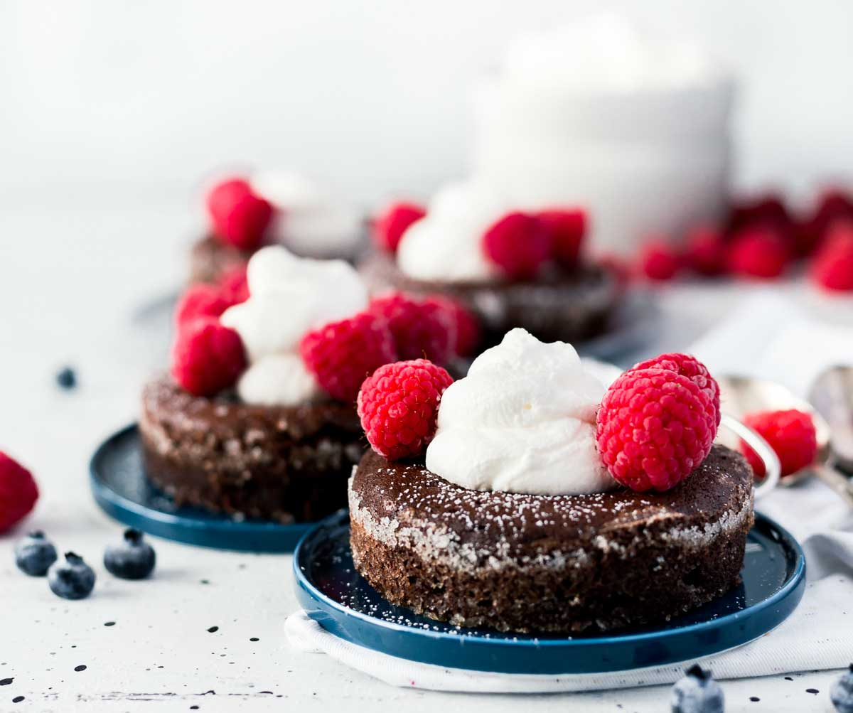 Soft Centered Fudge Cakes served with whipped cream, raspberries, and blueberries