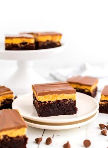 A brownie on a plate with chocolate chips scattered around.
