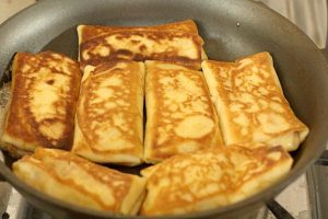 Process shot of making Strawberry and Cream Blintzes in a skillet