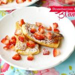 Strawberries and Cream Cheese Blintzes on a plate with text overlay for Pinterest