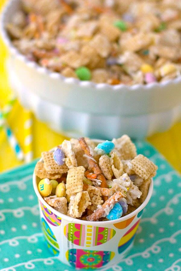 Bunny Bait Snack Mix in a decorative paper cup on top of a pretty blue napkin.