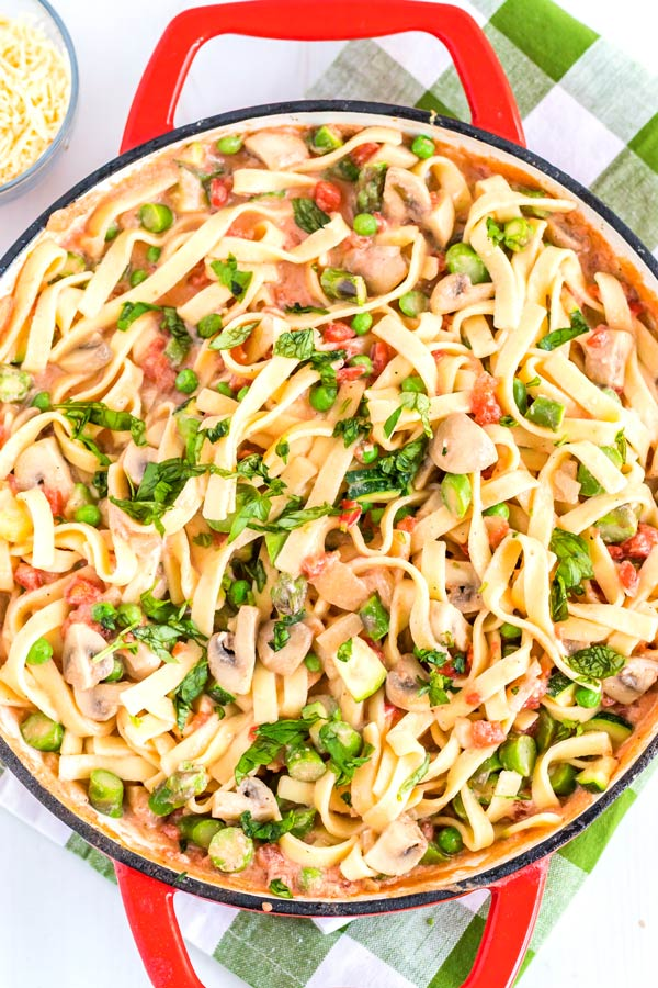 A close up overhead picture of pasta, veggies, and creamy sauce.