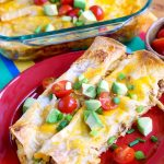 Breakfast Enchiladas on a plate with a baking dish in the background