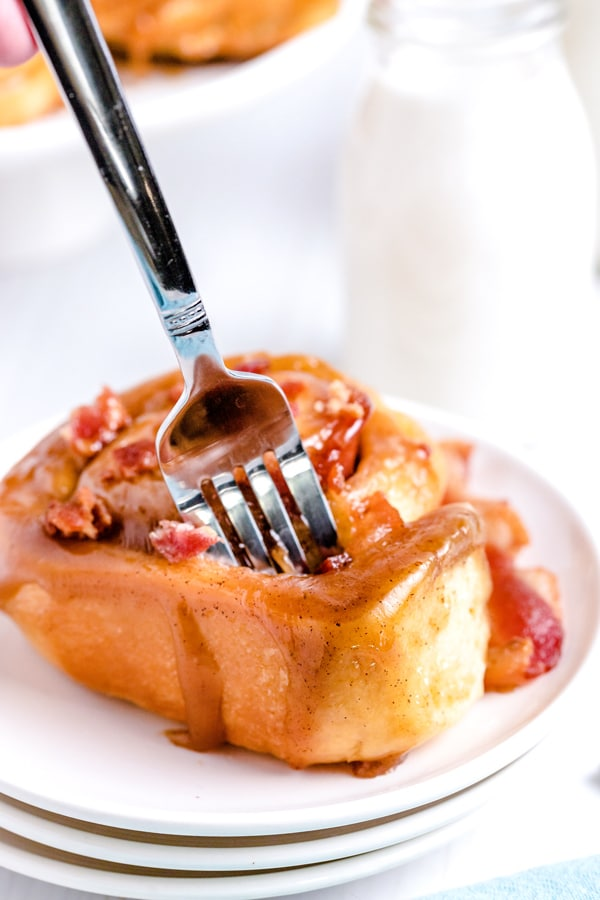 A fork digging into a sticky bun with bacon.