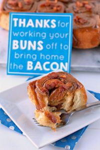 A sticky bun with bacon on a white plate and a Father's Day card in the background.