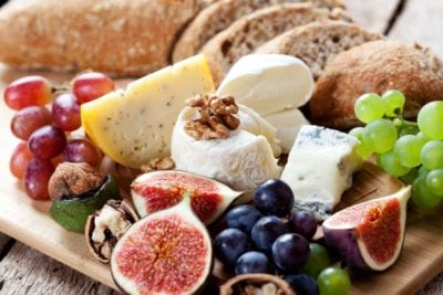 Close up picture of cheese, fruit, nuts, and bread on a cheese plate.