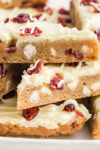 A closeup of cranberry bliss bars stacked on top of each other.