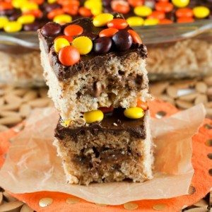 2 Reese's Rice Krispie Treats stacked on top of each other with a pan of them in the background.