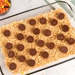 Pour half of the Rice Krispies mixture into the pan and lay the peanut butter cups on top.