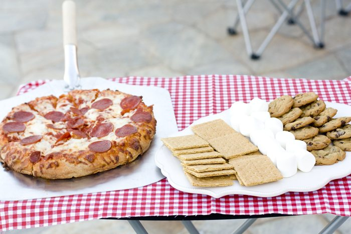 Pizza and s'mores try on a table.