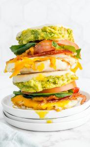 Two loaded Breakfast Sandwiches stacked on top of each other on a white plate.