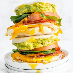 Breakfast sandwiches stacked on top of each other with runny yolks.