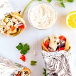 An overhead picture of 3 Chicken souvlaki pitas wrapped up in foil.