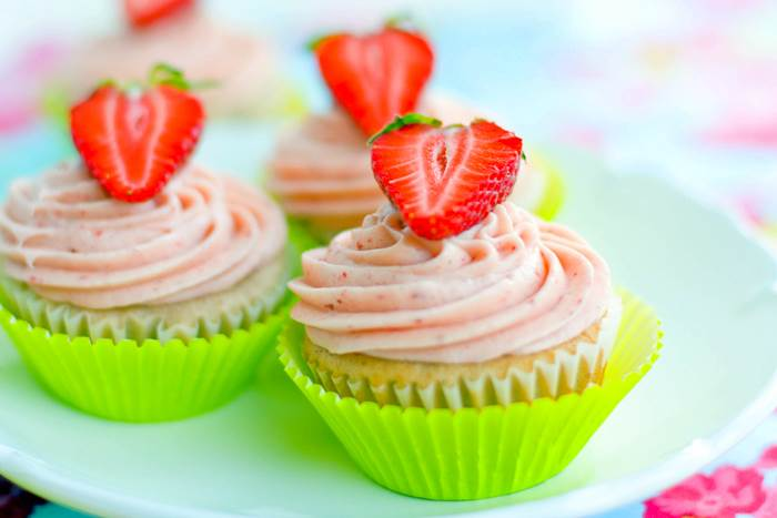 Three Fresh Strawberry Cupcakes on a white plate.