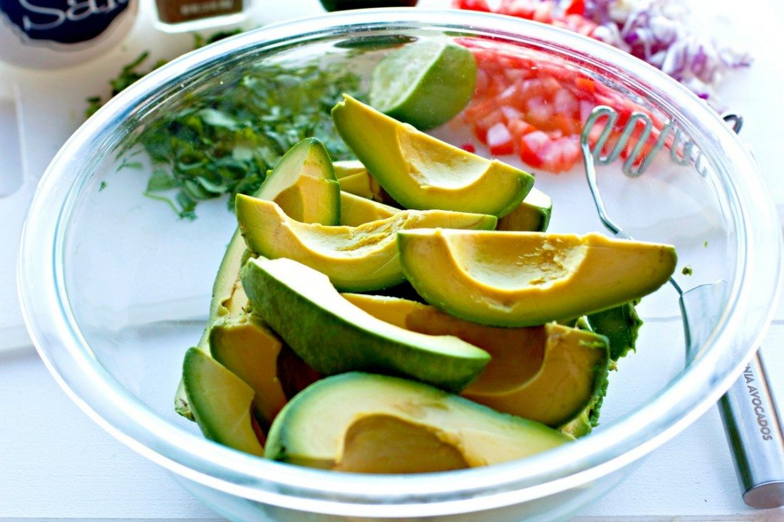 Place peeled and quartered avocados in a bowl.