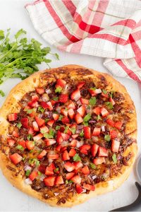 Sprinkle the pizza with chopped strawberries and cilantro.